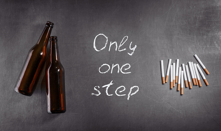 batch: Concept of  beer bottles and cigarettes batch on gray background with lettering: from alcohol to cigarettes only one step