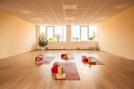 empty bright yoga room with mats and requisite.
