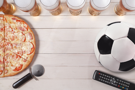 glasses of beer with pizza and soccer ball. Copy space.