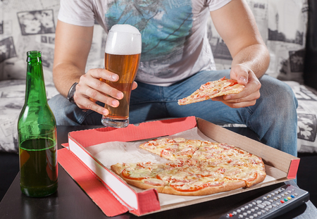 Closeup of man holding pizza slice and beer. Wath TV.