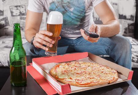 ver television: El hombre ver la televisión y comiendo pizza con cerveza. De cerca. Sentado en el sofá