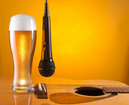 bard: microphone hangs beside glass of beer on guitar. yellow background. empty space for text Stock Photo