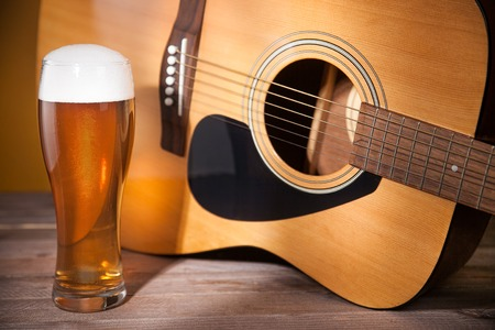 glass of beer with froth near acoustic guitar on wooden table.