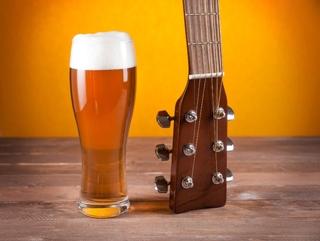 glass of beer next to guitar fretboard on wooden table.