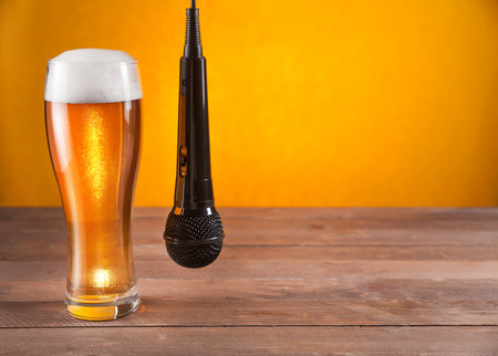 De microfoon hangt naast glas bier. gele achtergrond. lege ruimte voor tekst