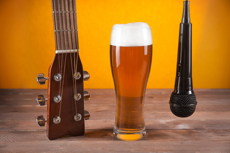 near beer: glass of beer and microphone near to guitar fretboard on wooden table. Stock Photo