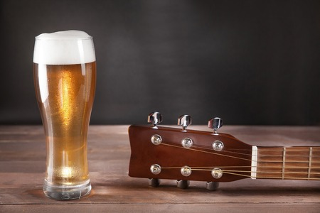 glas bier naast gitaar toets op houten tafel.