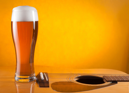glass of beer standing on guitar. yellow background. empty space for text
