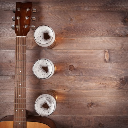 top view of few glasses beer near neck acoustic guitar on wooden table. Blank space for text.