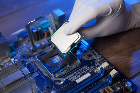 white glove: engineer in white glove sets processor to motherboard. closeup.