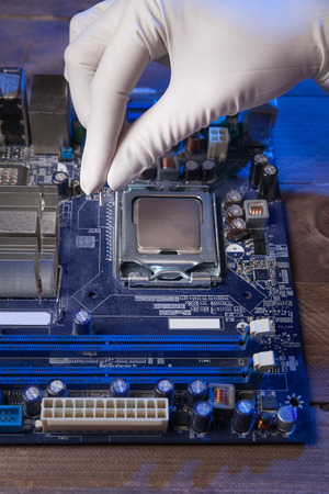 engineer in white glove sets processor to motherboard. closeup.