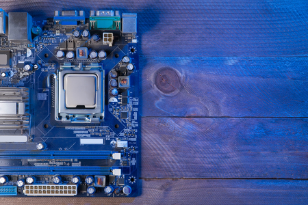Top view of the motherboard lying on wooden table. Blank space for text.