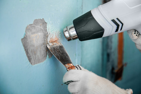 Master removes old paint from concrete wall with heat gun and scraper. Closeup