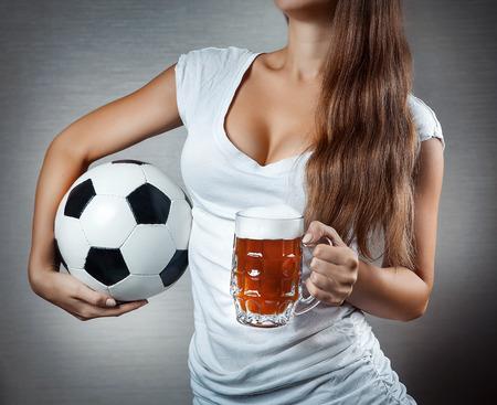 jonge sexy vrouw met voetbal en bier mok. Open de borst. Detailopname. Stockfoto