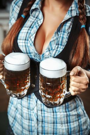 jonge sexy oktoberfest vrouw met twee donkere bierpullen. Open de borst. Focus op mokken.