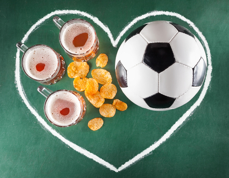 alphabet beer: Sport bar set from beer mugs, chips and soccer ball in drawing heart on green background. Stock Photo