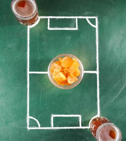Twee biermokken op miniatuurvoetbalgebied met plaat van spaanders.