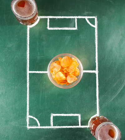 Two beer mugs on miniature soccer field with plate of chips.