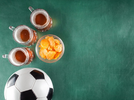 mugs of beer with snack and soccer ball  on green background. Free space for text.