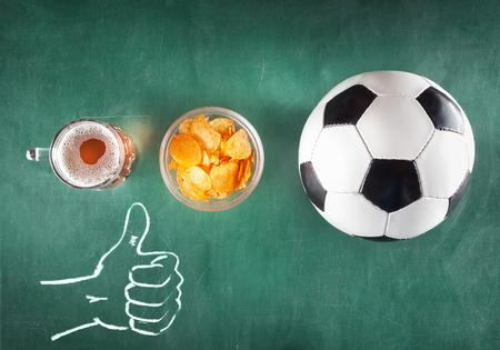mok bier met snack en voetbal bal op groene achtergrond. Duim omhoog. Stockfoto
