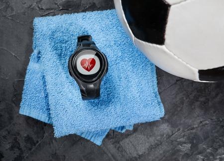hartslagmeter op blauwe handdoek in de buurt van voetbal.