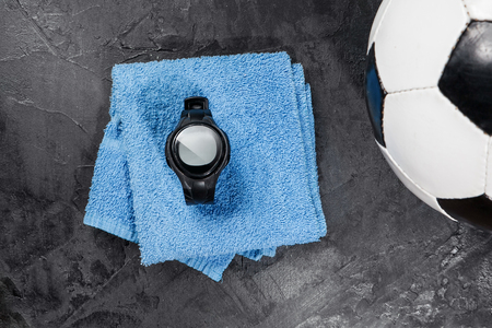 heart rate monitor on blue towel near soccer ball.