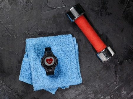 heart rate monitor on blue towel near red dumbbel. 版權商用圖片