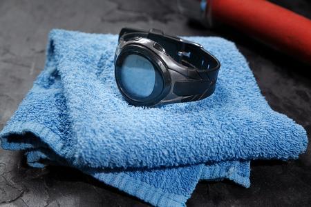hartslagmeter op blauwe handdoek in de buurt van rode dumbbel. Stockfoto
