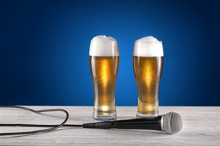 Two glass beer and microphone on white wooden desk. Blue background. Free space for text. Design 版權商用圖片