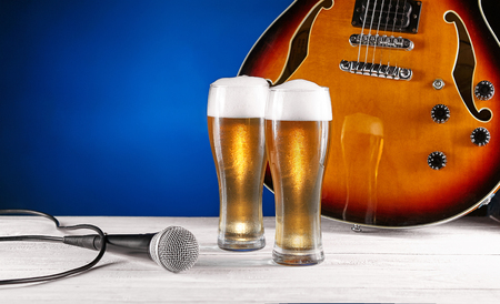 Two glass beer and microphone near electric jazz guitar on white wooden desk. Blue background. Free space for text. Design