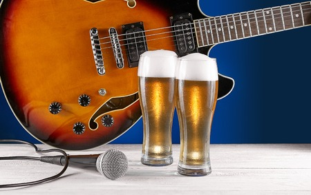Two glass beer and microphone near electric jazz guitar on white wooden desk. Blue background. 版權商用圖片