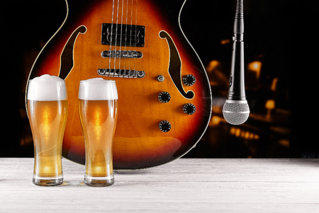Two glass beer and microphone near electric jazz guitar on white wooden desk. Dark background. 版權商用圖片