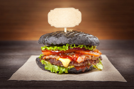 Black hamburger on the table.