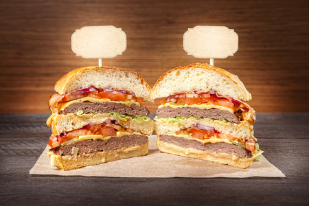 Halves hamburger with fried meat and vegetables on wrapping paper.Space for text.