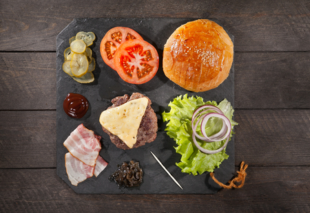 Ingredients for a hamburger on a slate board. top view