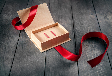 Gift kraft packing with red ribbon on wooden table. 版權商用圖片