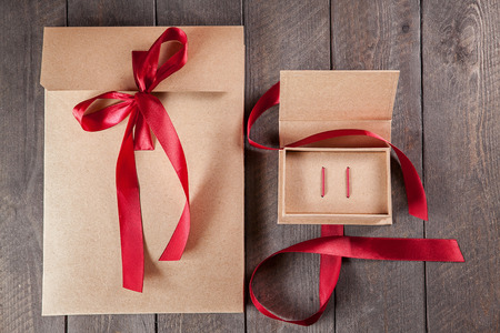 Gift kraft packing with red ribbon on wooden table. top view.