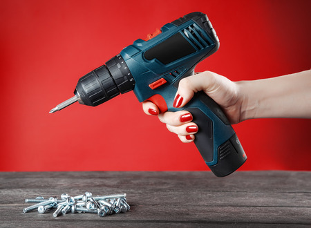 Girl with nailed-up nails holds in her hand blue electric screwdriver and bolts on wooden table. close-up. Red background.