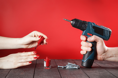Concept of confronting domestic male and female worries. Female hand paints fingernails, and man's hand holds electric screwdriver. Close-up on wooden table. Red background.