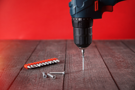Twisting screw with blue electric screwdriver into  black wood. close-up. Red background.