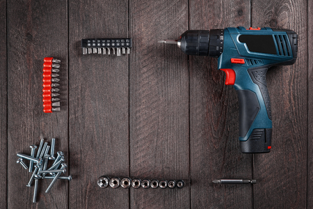 Blue electric screwdriver lies on  black wooden table with bolts and bits. Top view. Free space for text.