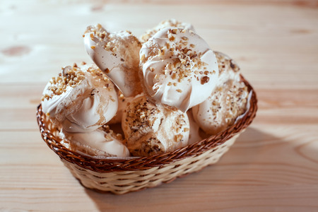 meringue with nuts in basket on wooden background on bright morning. 版權商用圖片