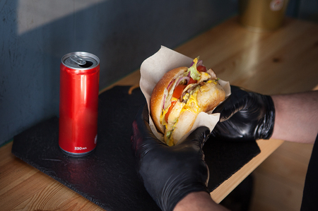 lunch from delicious hamburger in male hands in black rubber gloves next next to drink in an aluminum can.