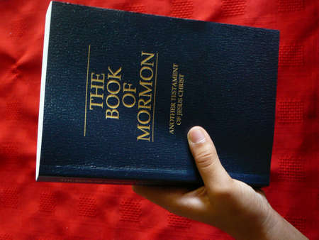mormon: Hand picking up the Book Of Mormon.