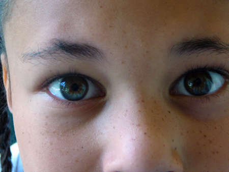 Close-up of a freckle-faced girl with beautiful eyes.
