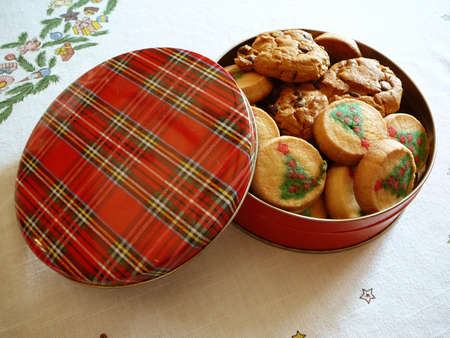 Cookies decorated like Christmas trees in a Tartan plaid tin. photo