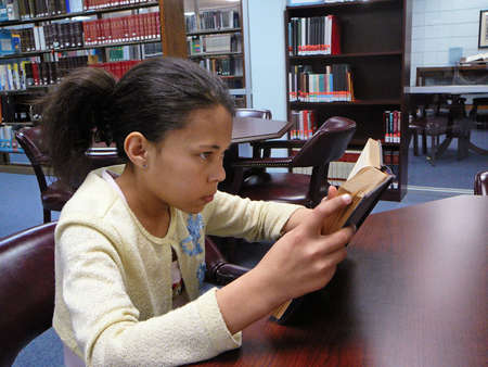 Child studying in the library. photo