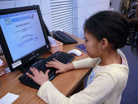 Child using library computer. photo
