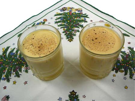 egg nog: Two glasses of egg nog on a Christmas napkin