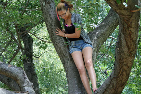 Girl in gnarled Southern Magnolia tree Stock Photo